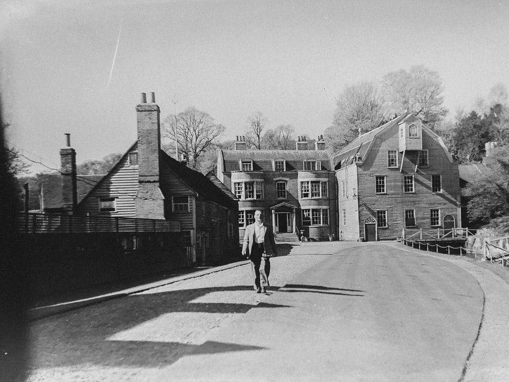 man walking alone on road near houses
