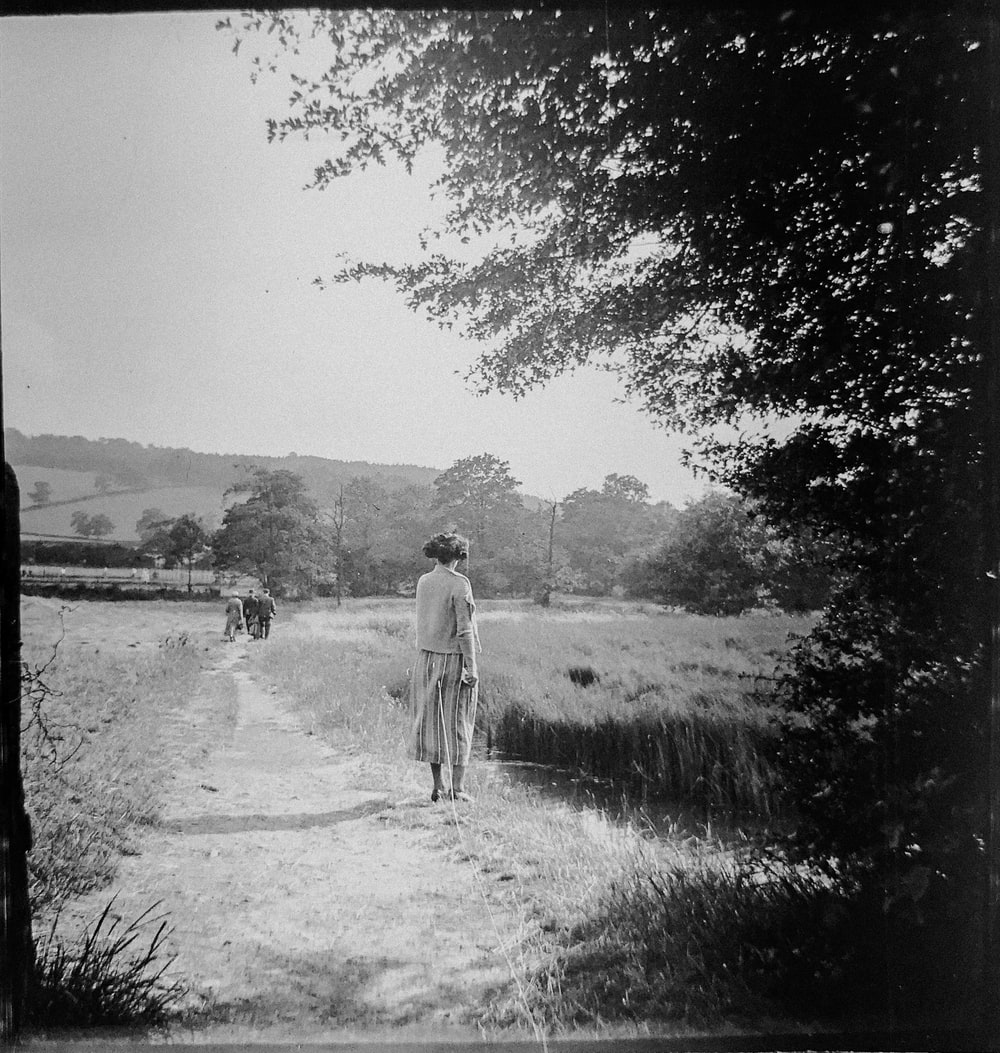 women in a field gray-scale photography