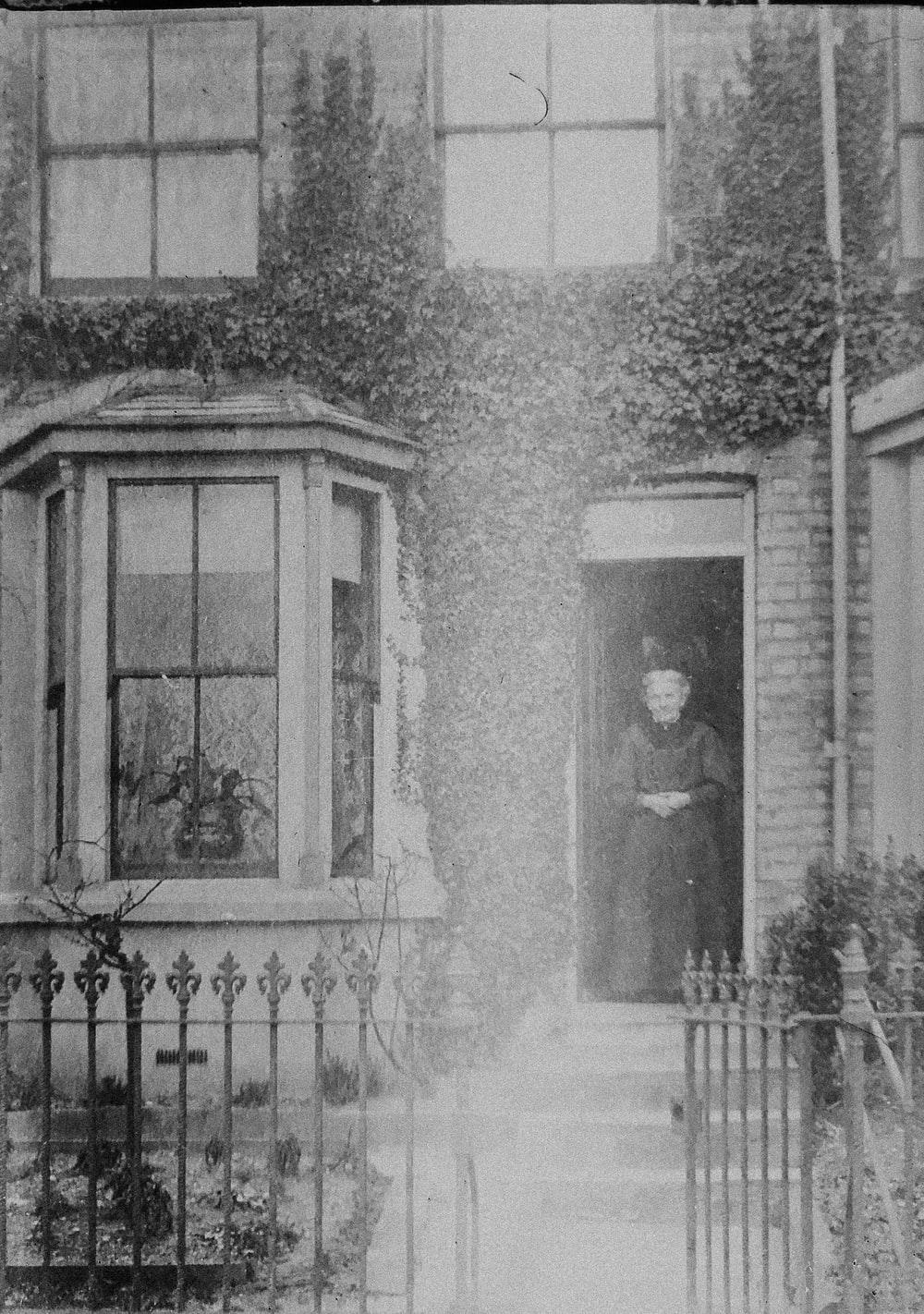 grayscale photo of 2 women standing in front of window