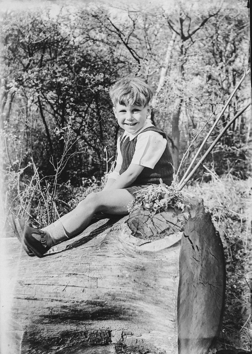 grayscale photo of boy on tree log