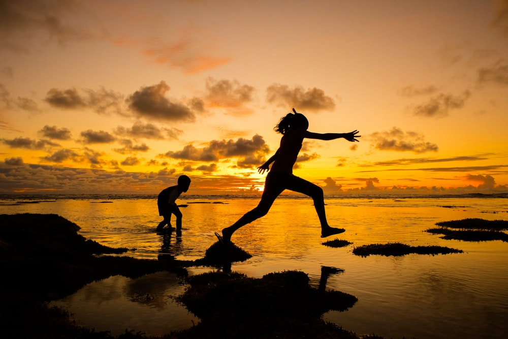 silhouette of girl and boy at the beach
