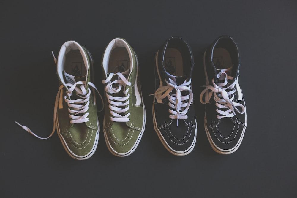two pairs of black green-and-black Vans Sk8-Hi sneakers