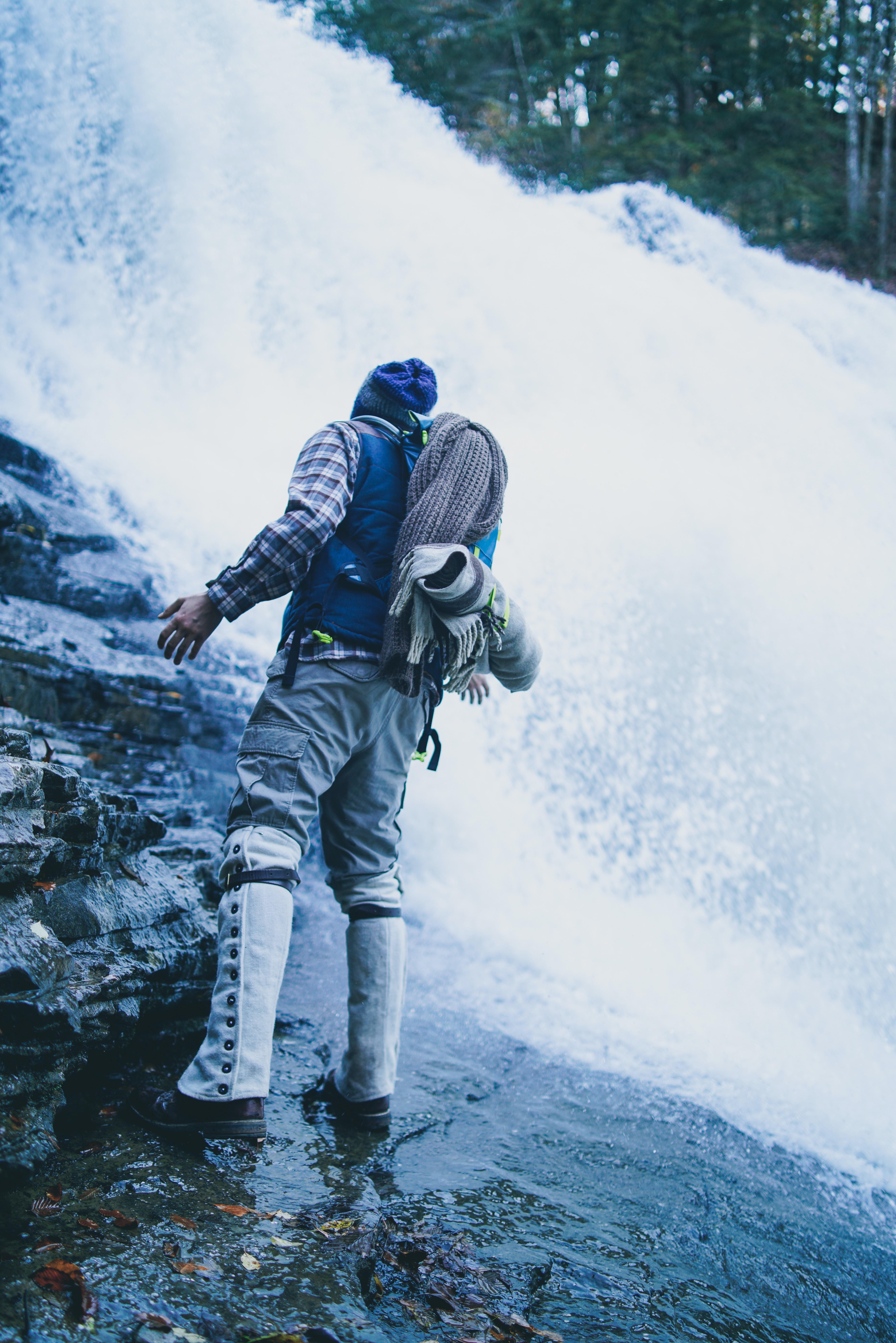 man standing on waterfall