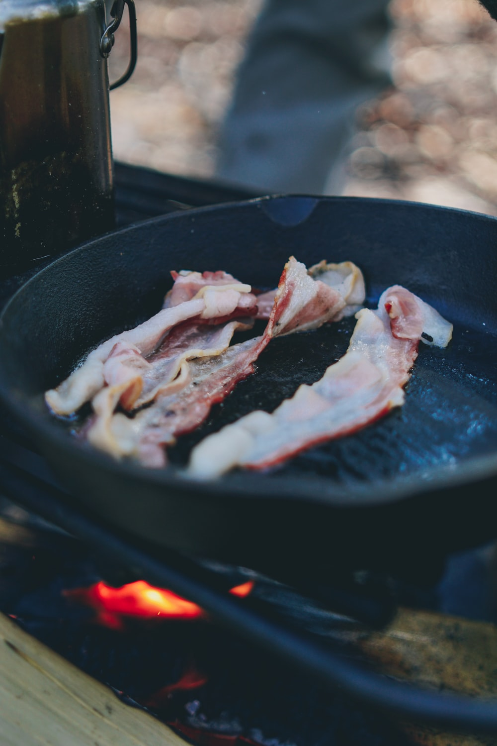 bacon strips on black cast iron frying pan