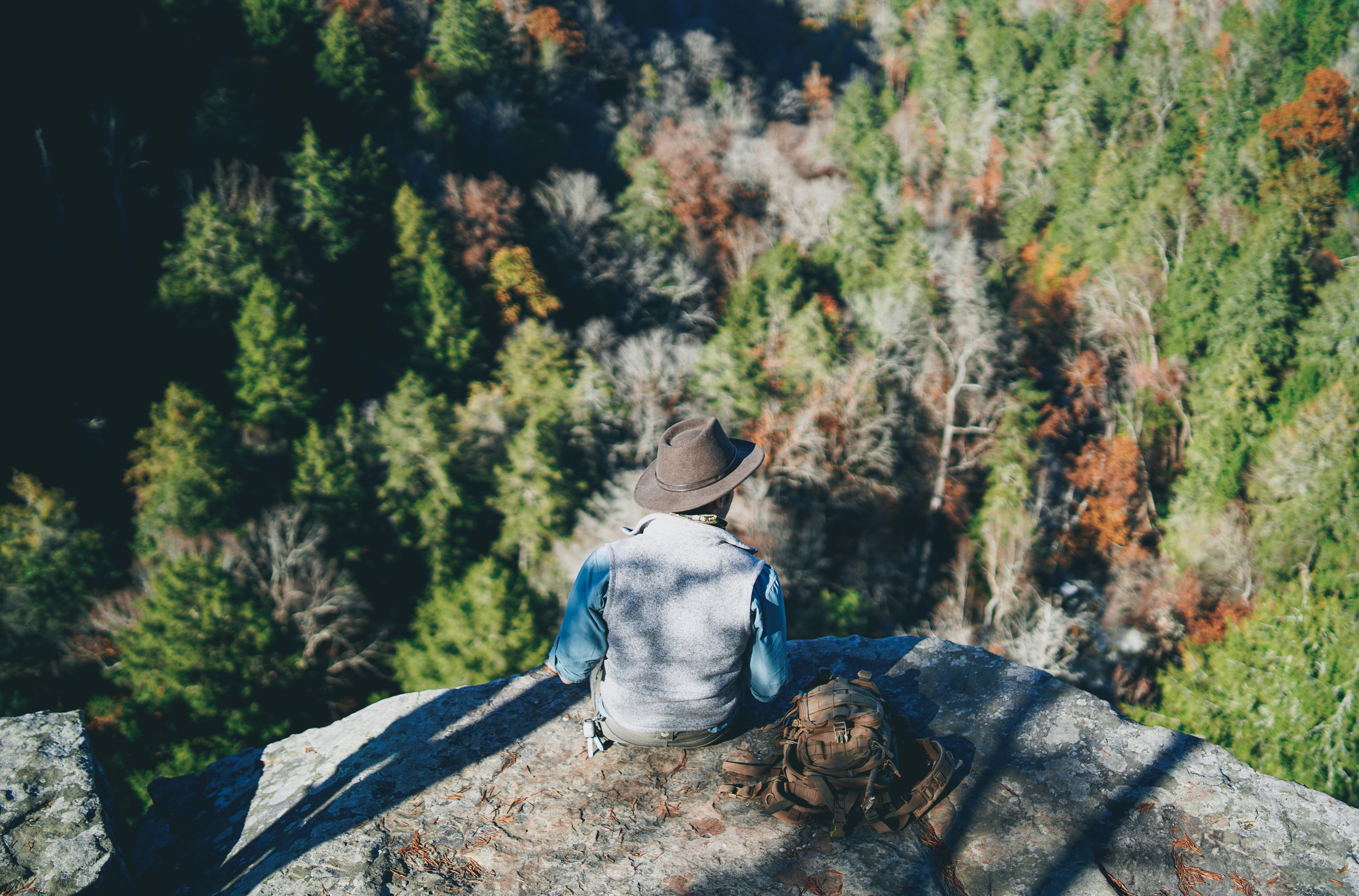 aerial view photography of man sitting on cliff during daytime