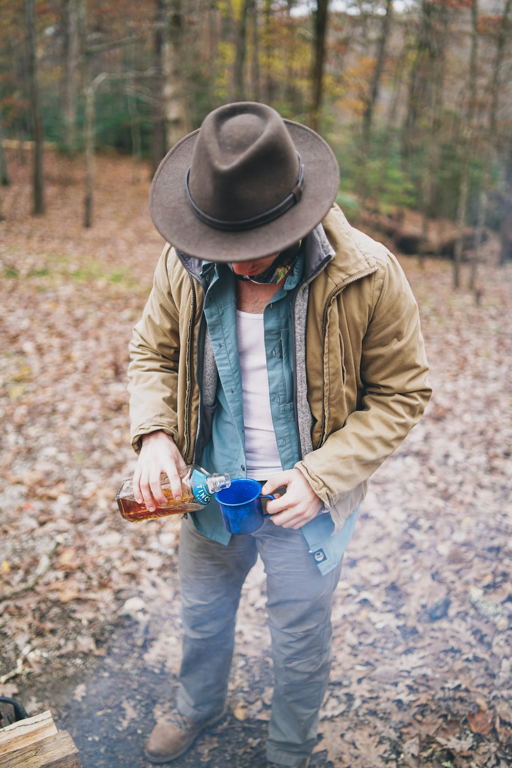 man wearing brown hat pouring liquid on blue cup
