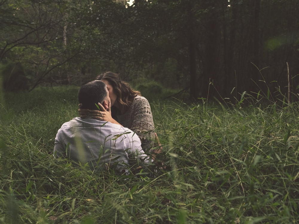 man and woman kissing on green grass field