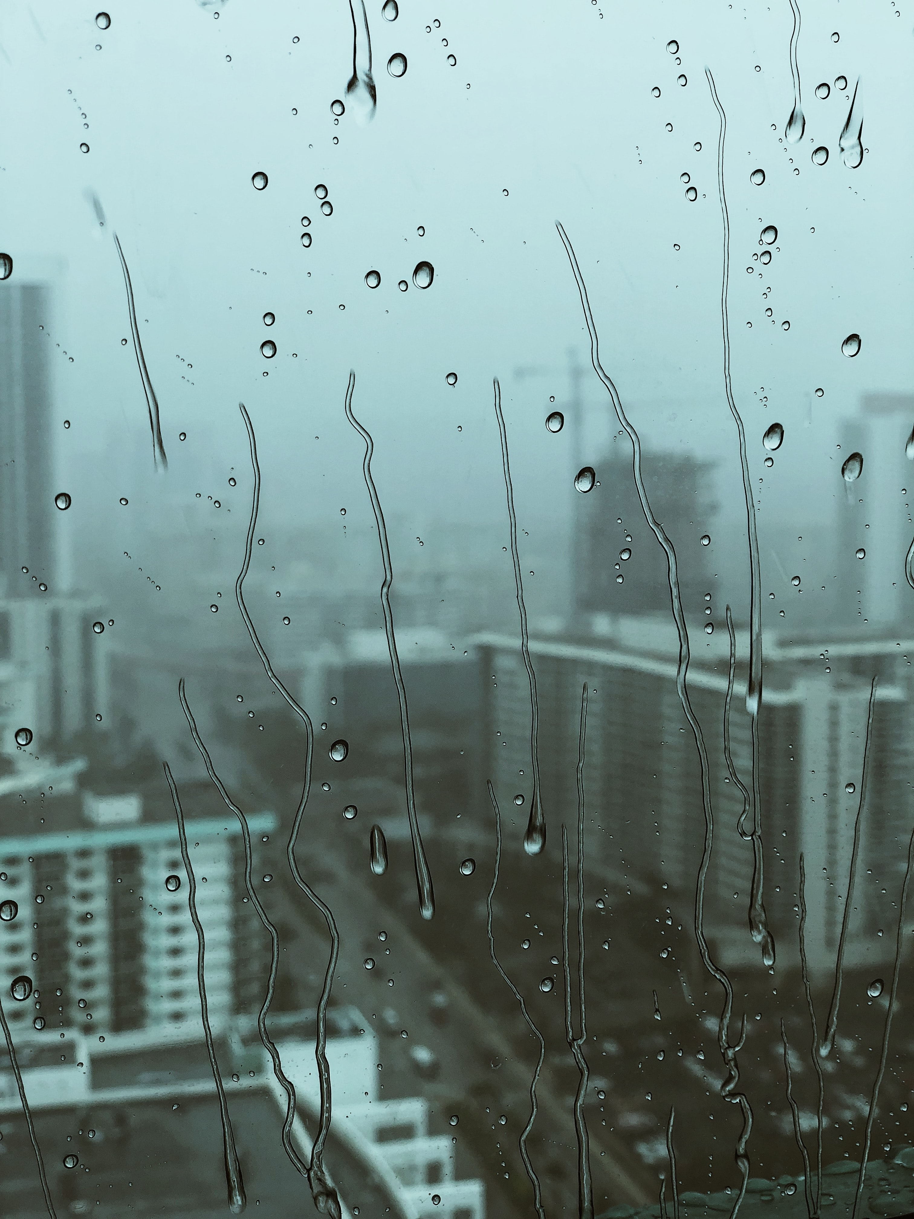 view of cityscape from glass with water droplets