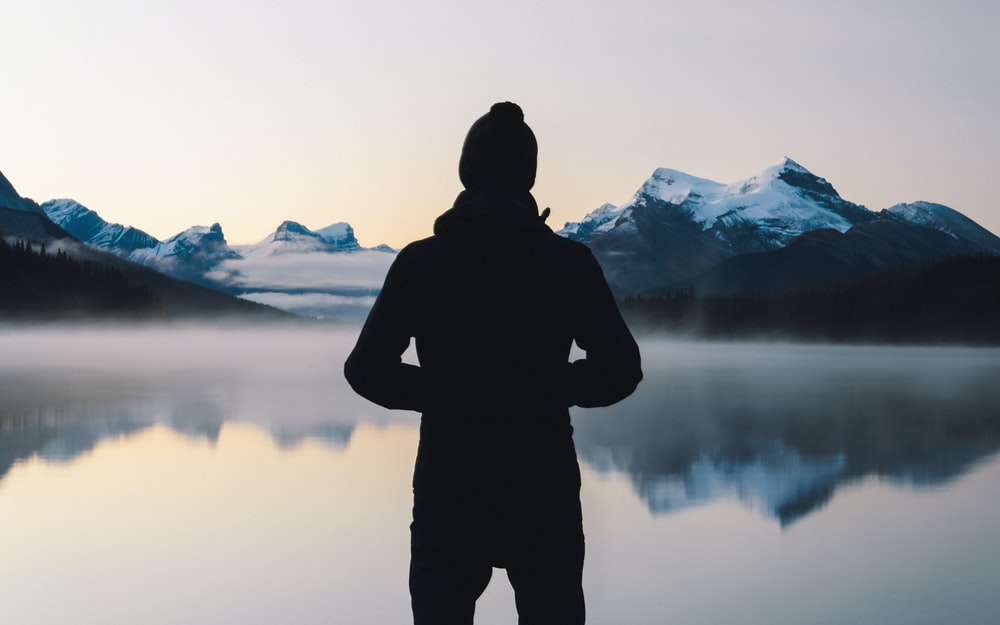 person standing in front of body of water outdoors