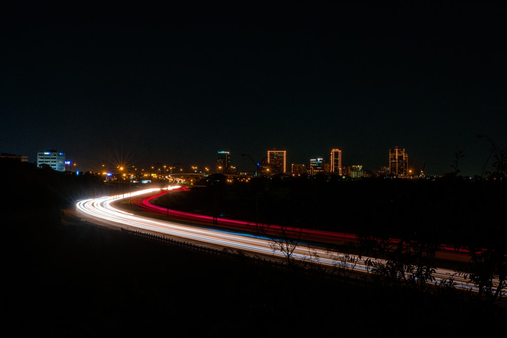 white and red neon lights passing on road at night