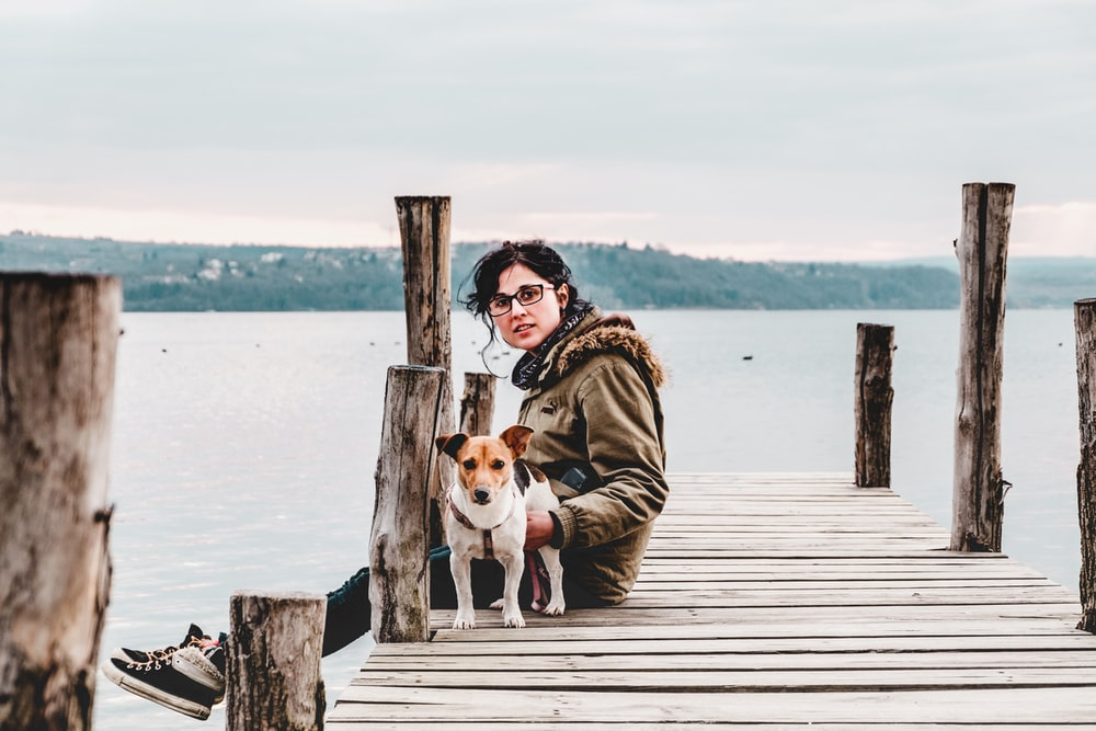 woman sitting on brown wooden dock with dog