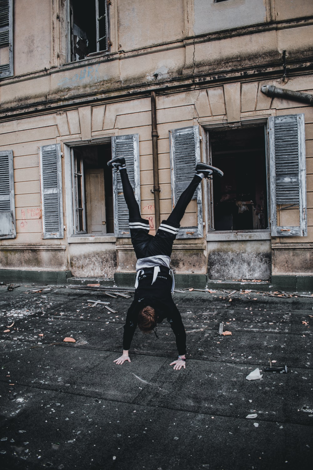 man doing hand stand on street near building during daytime