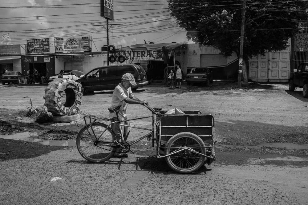 grayscale photography of man holding bicycle