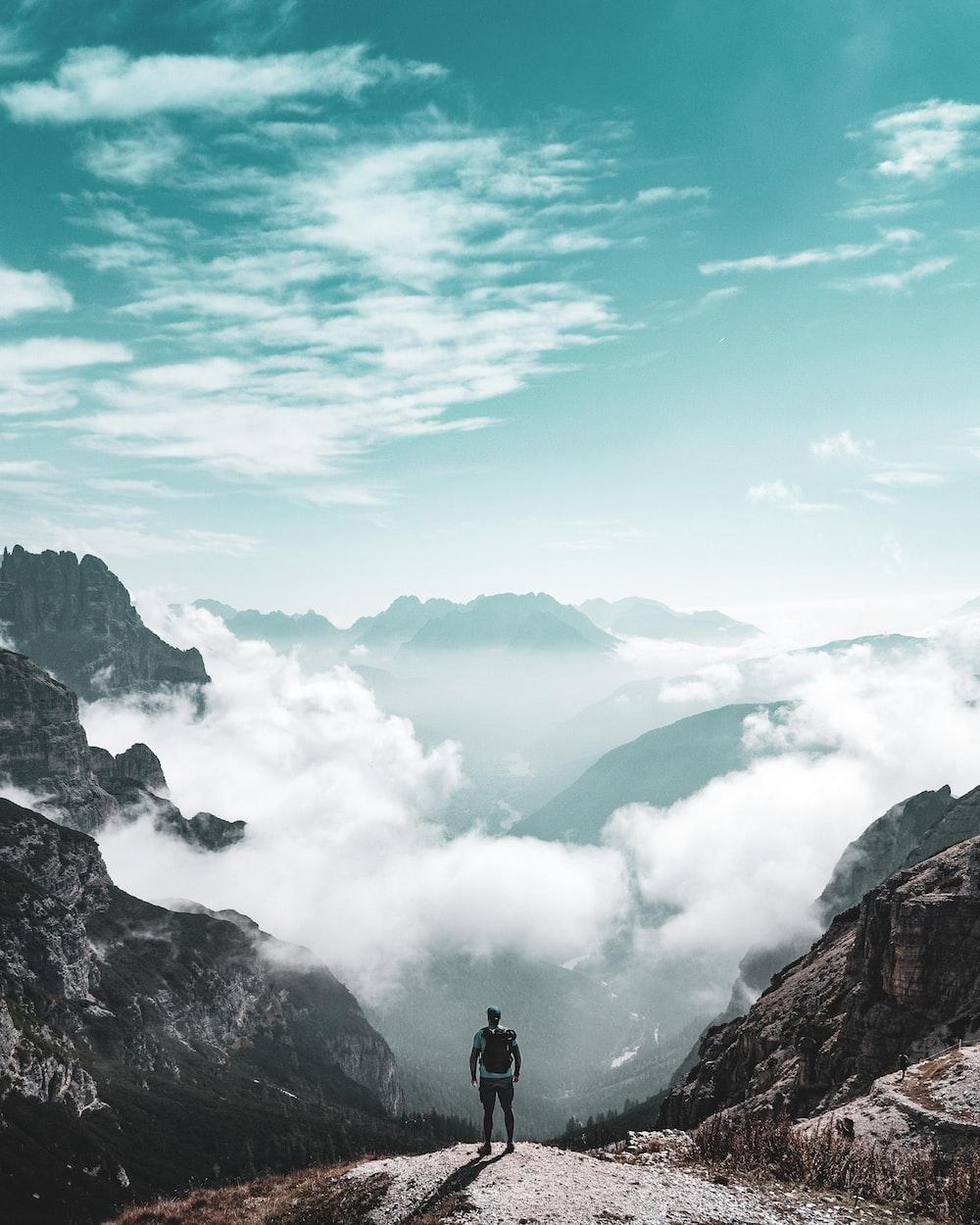 man on hill near mountains