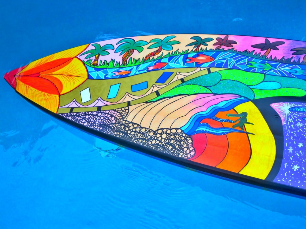 multicolored surfboard on body of water