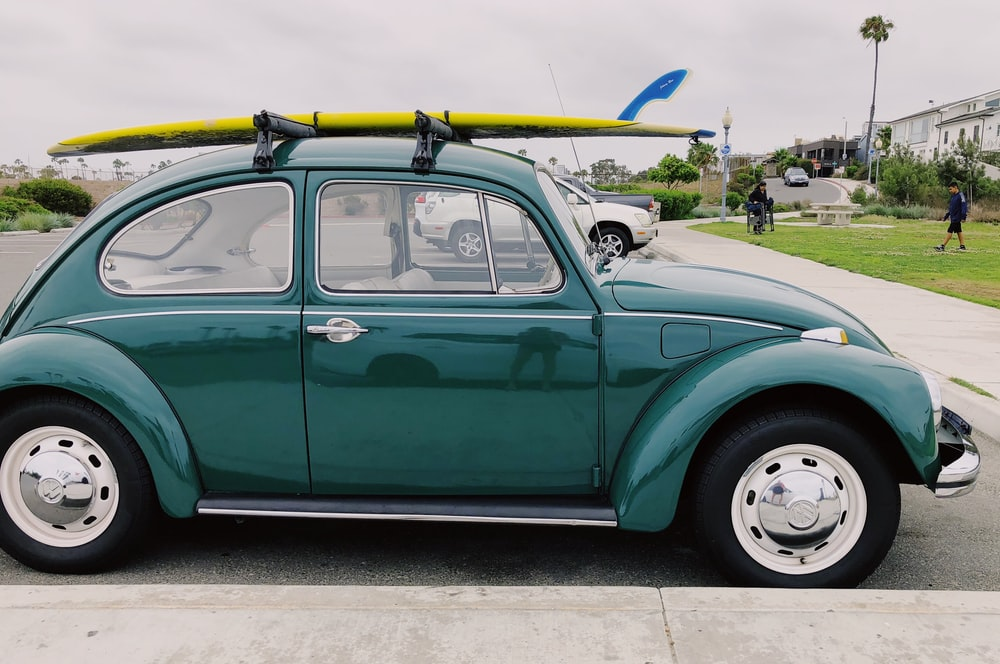 empty green Volkswagen Beetle carrying yellow surfboard on parking lot during daytime