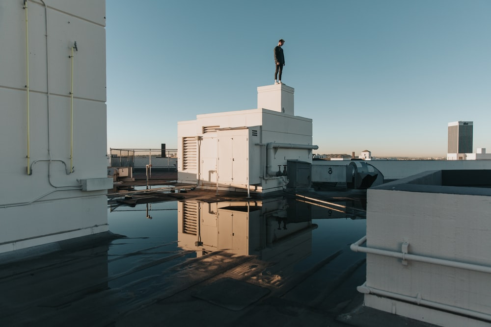 man stand on white building