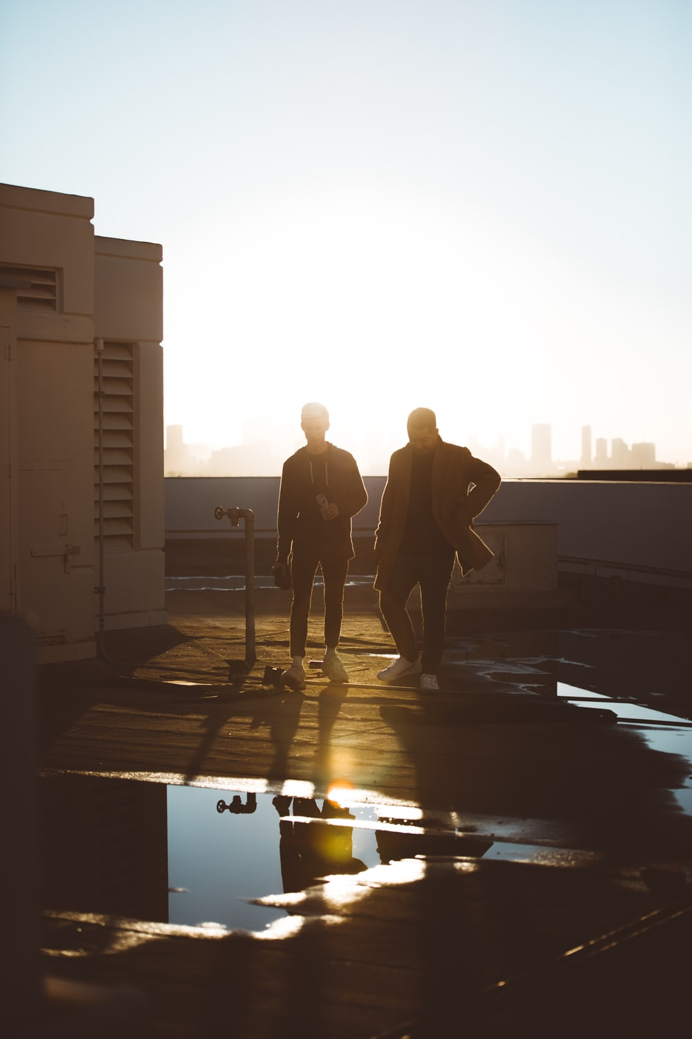two men standing on rooftop