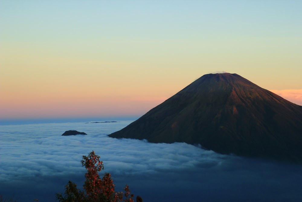 high-angle photography of volcano and clouds