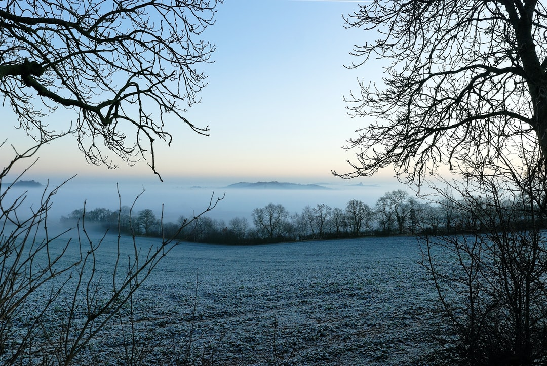Looking out over a cold and frosty Cotswold countryside complete with mist created by and trapped by a thermal inversion layer in the valley bottom.  This gives a very flat top to the mist and can be very effective.   In eight years living in this particularly hilly and frosty part of the Cotswold's, I only saw this a couple of times.