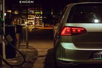 silver Volkswagen Golf station wagon parked beside gas pump during nighttime