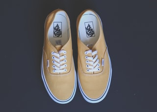 pair of yellow vans low-top shoes