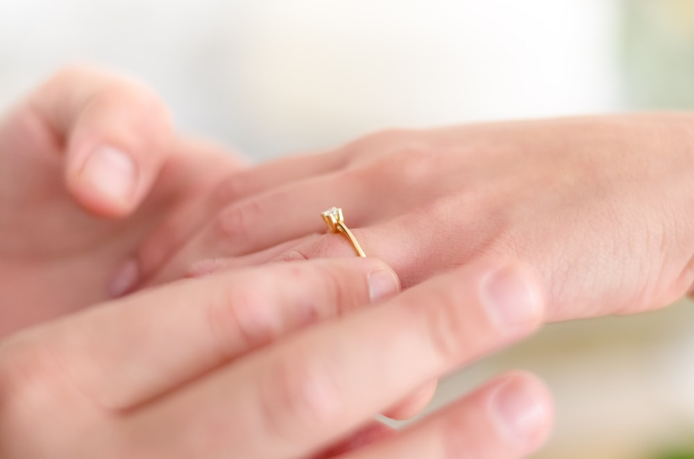 shallow focus photo of person putting gold-colored ring