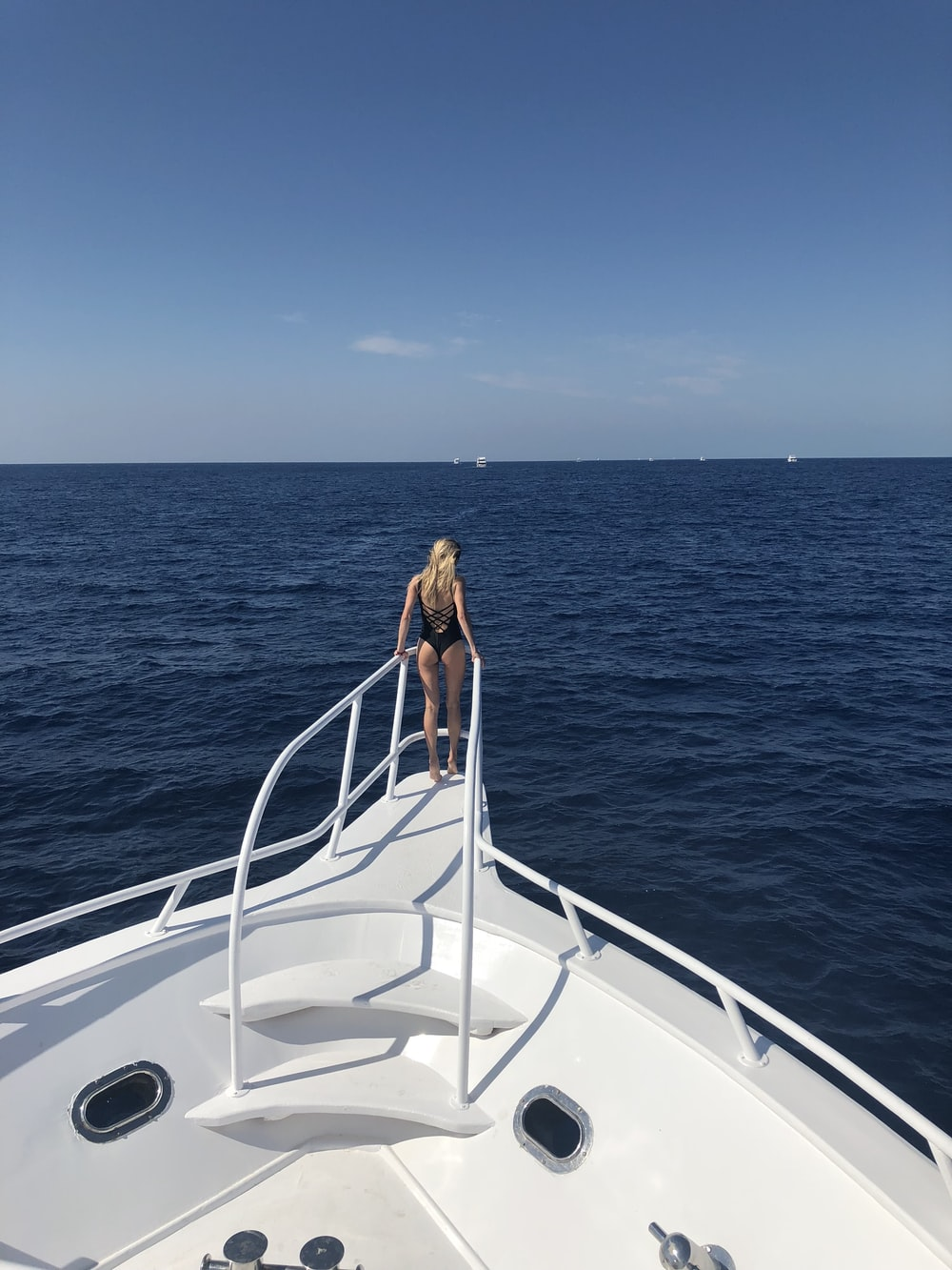 woman standing in front of white boat