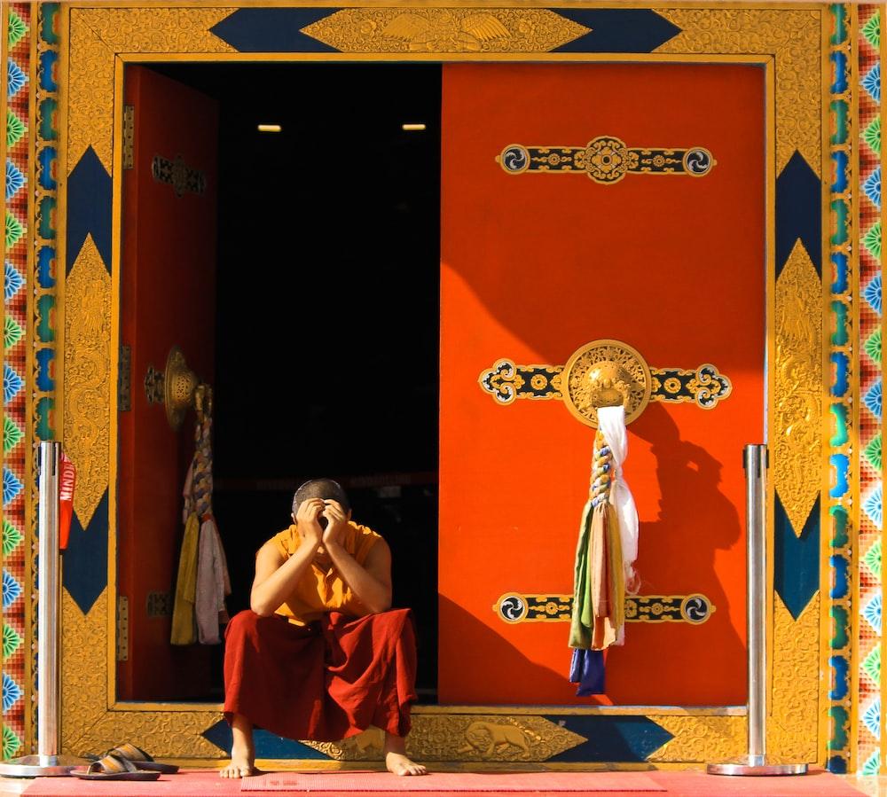 man in orange top sitting beside door