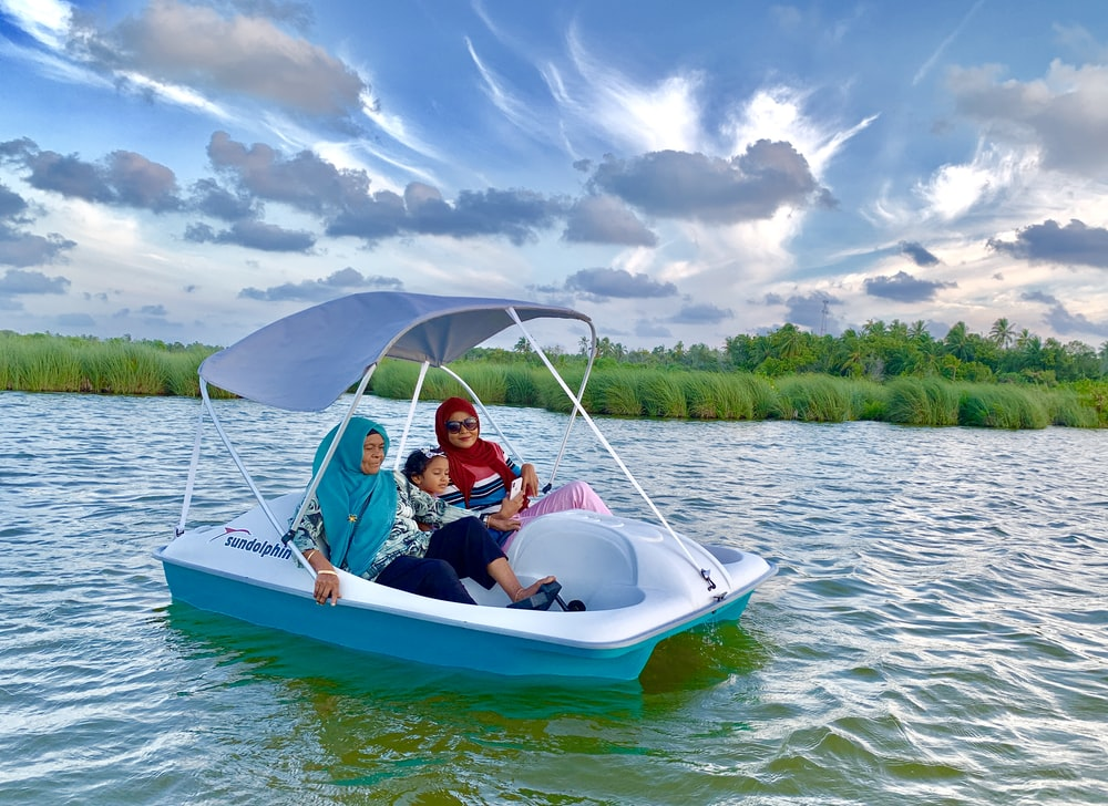 three person riding boat on body of water