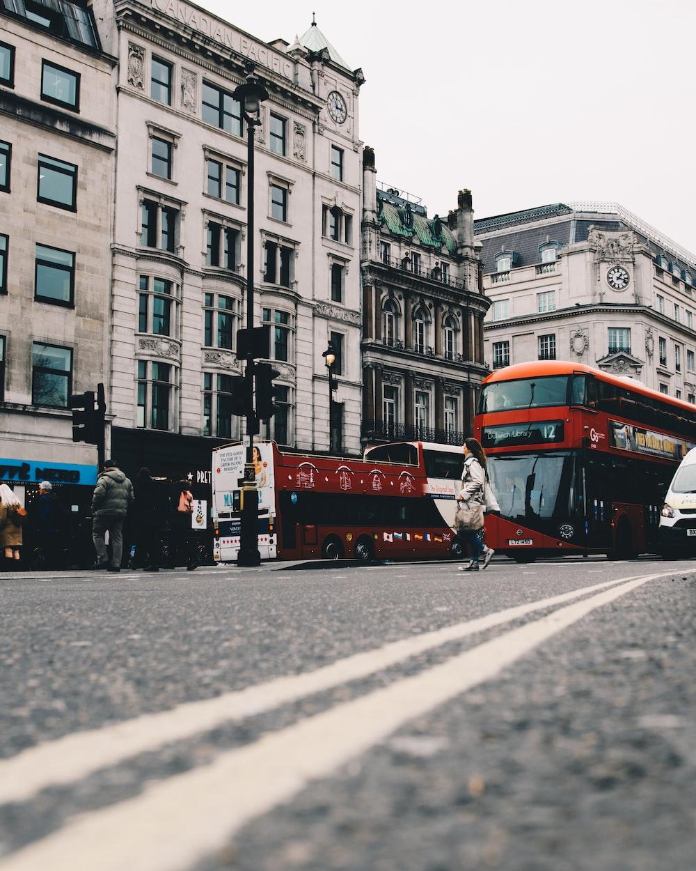 double-decker bus passing near white building