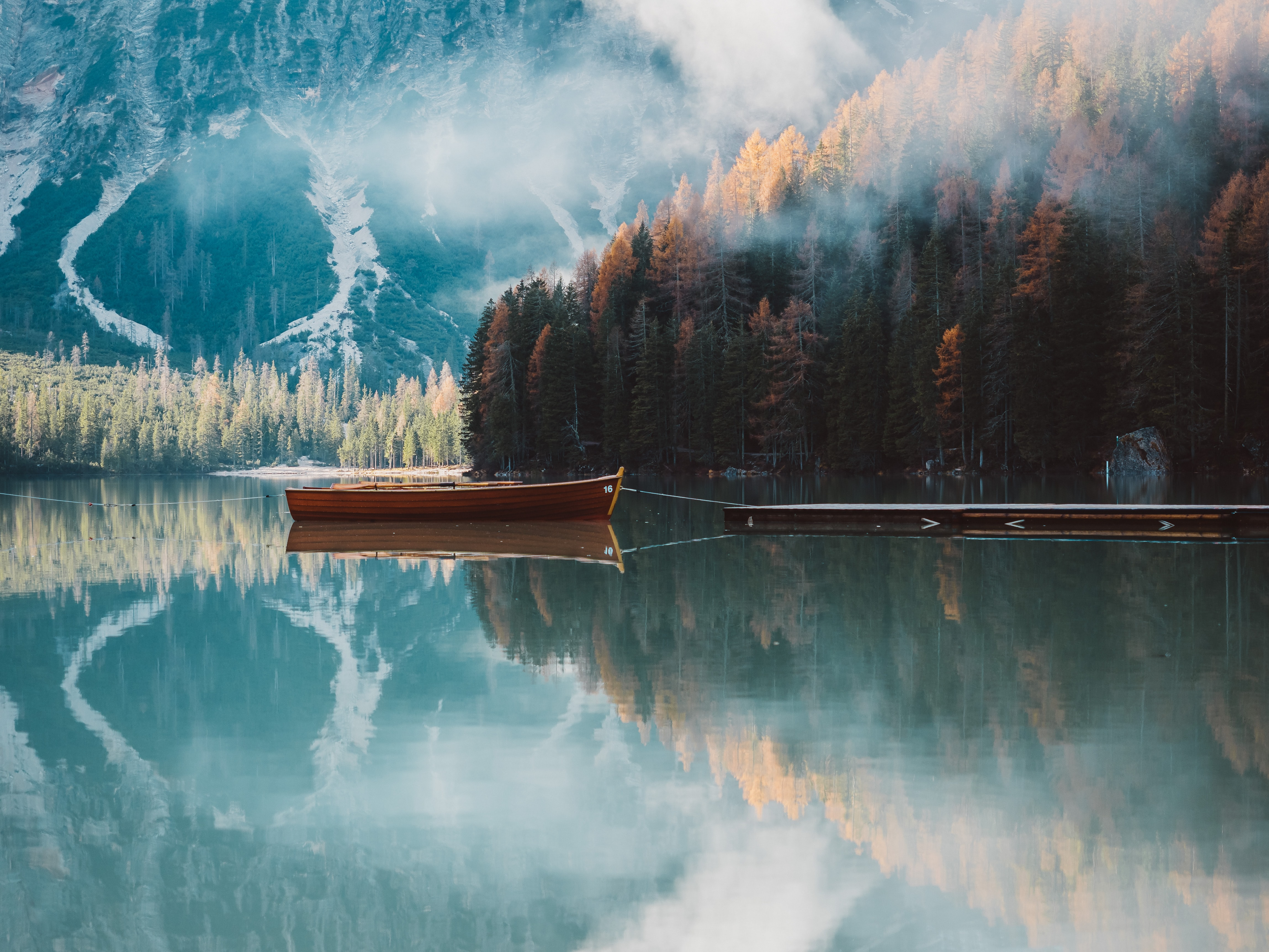 brown canoe on body of water near forest under fog