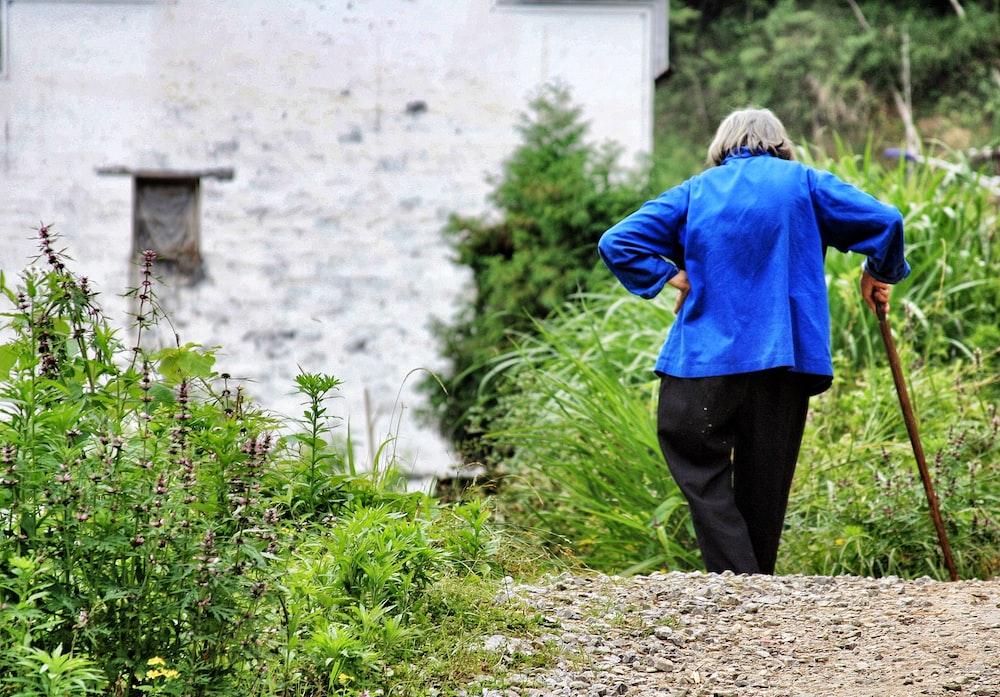 woman walking while holding walking cane