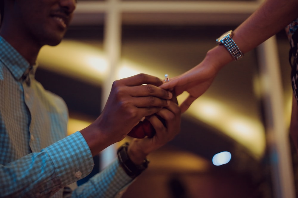 man putting ring on woman's hand