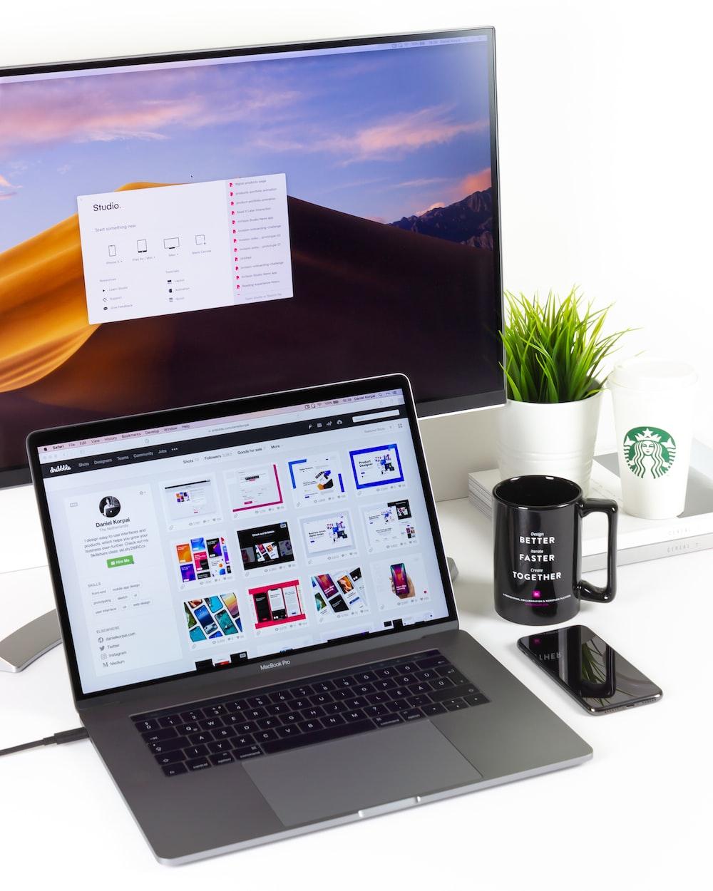 laptop near mug and computer monitor