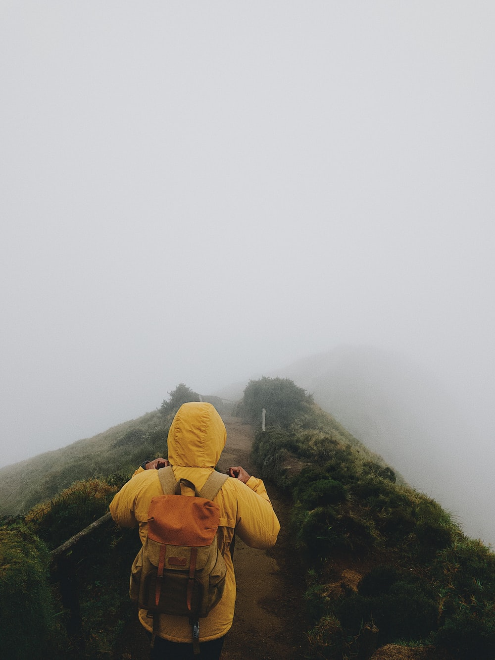 person in yellow coat wearing backpack