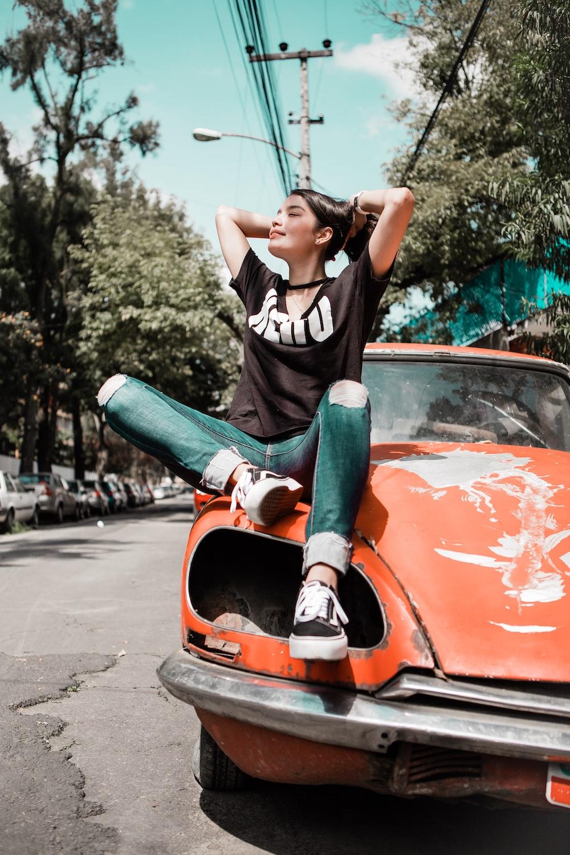 woman wearing black shirt sitting on orange vehicle
