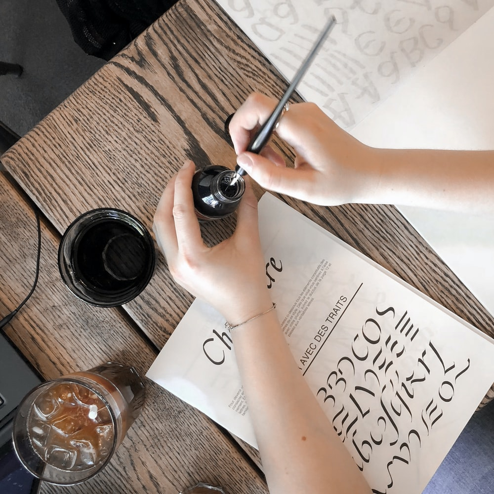 person holding bottle and pen over table with book and drinking glasses