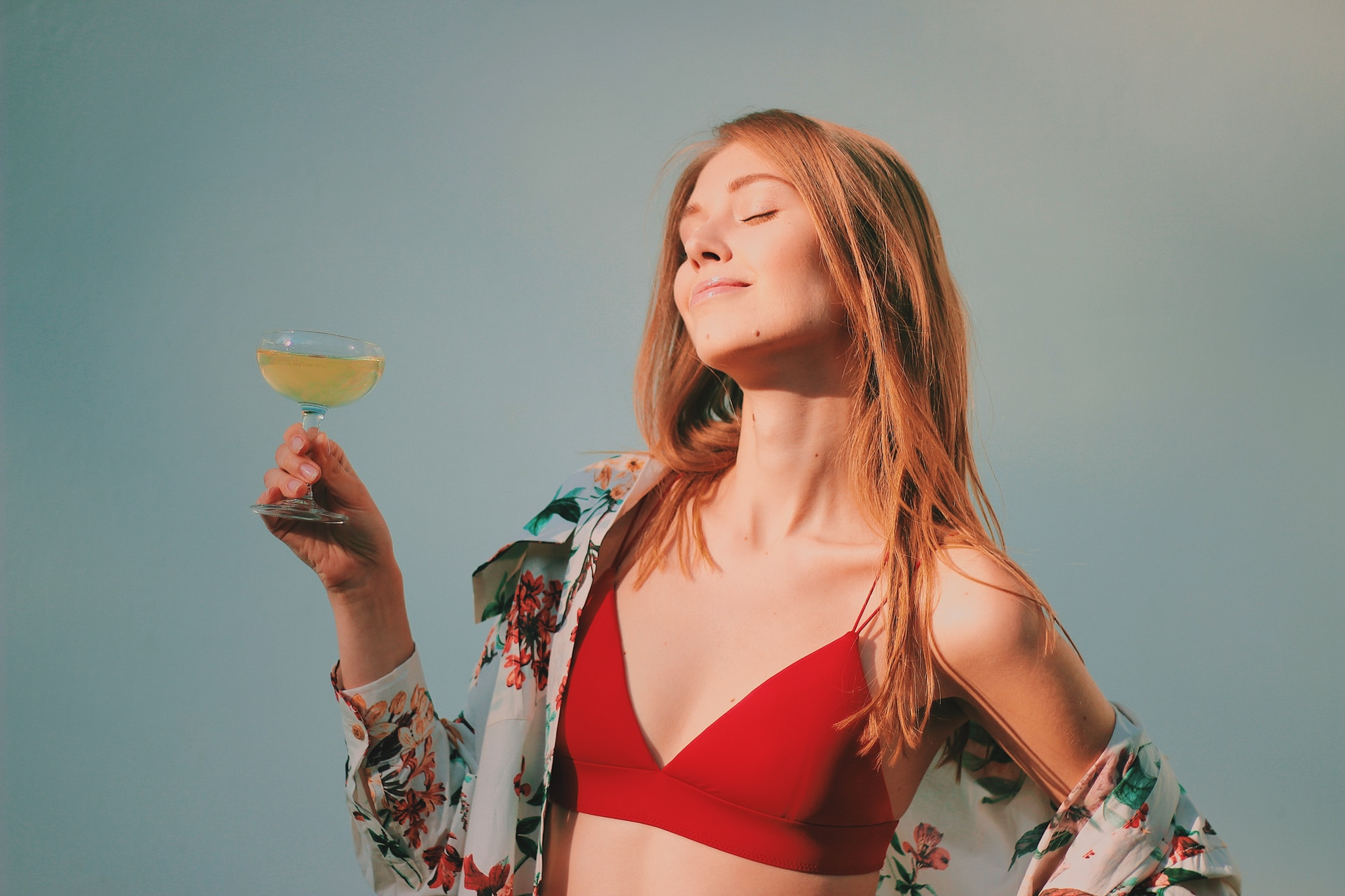 shallow focus photo of woman in red bikini top holding champagne glass