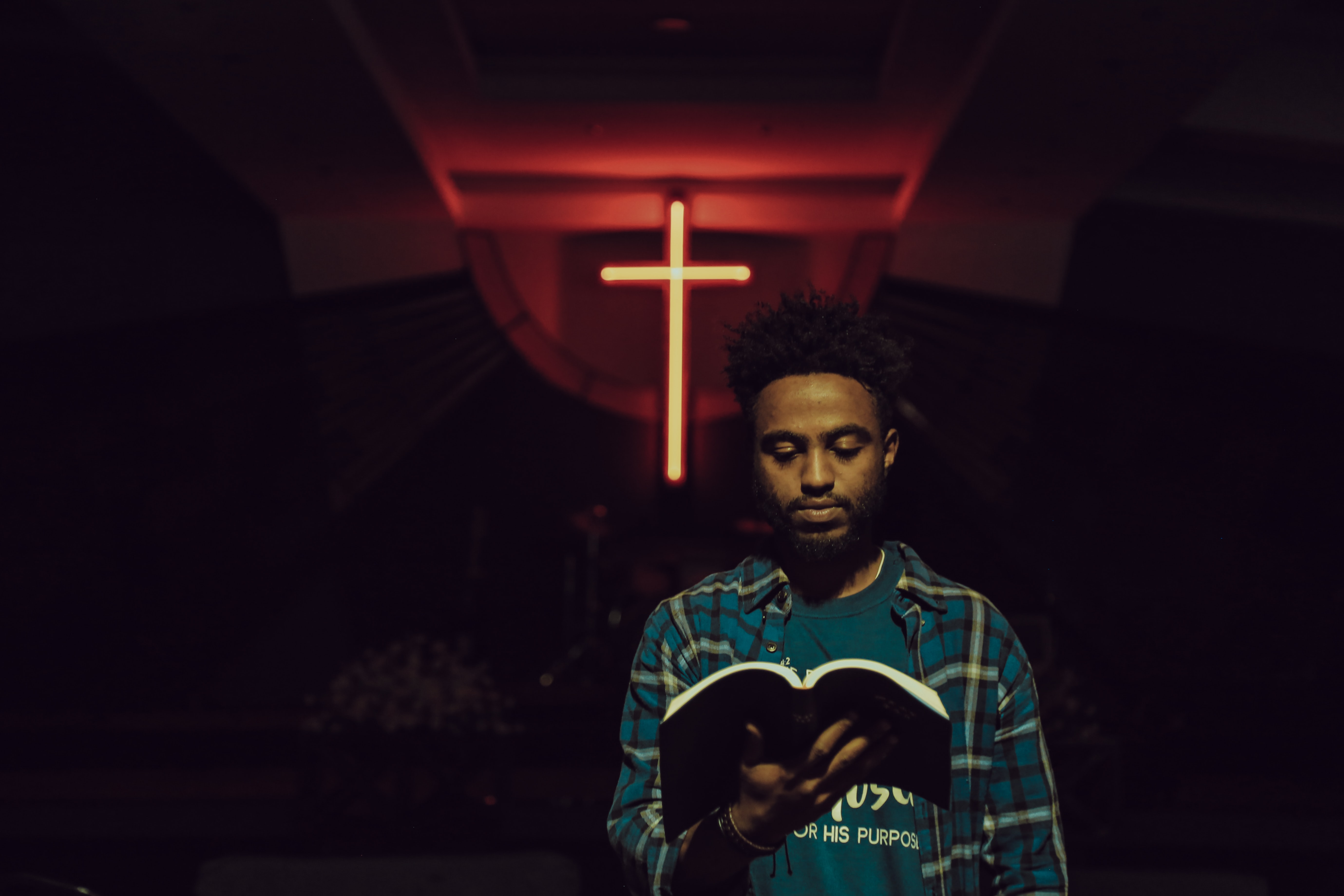 man reading book in front of LED cross