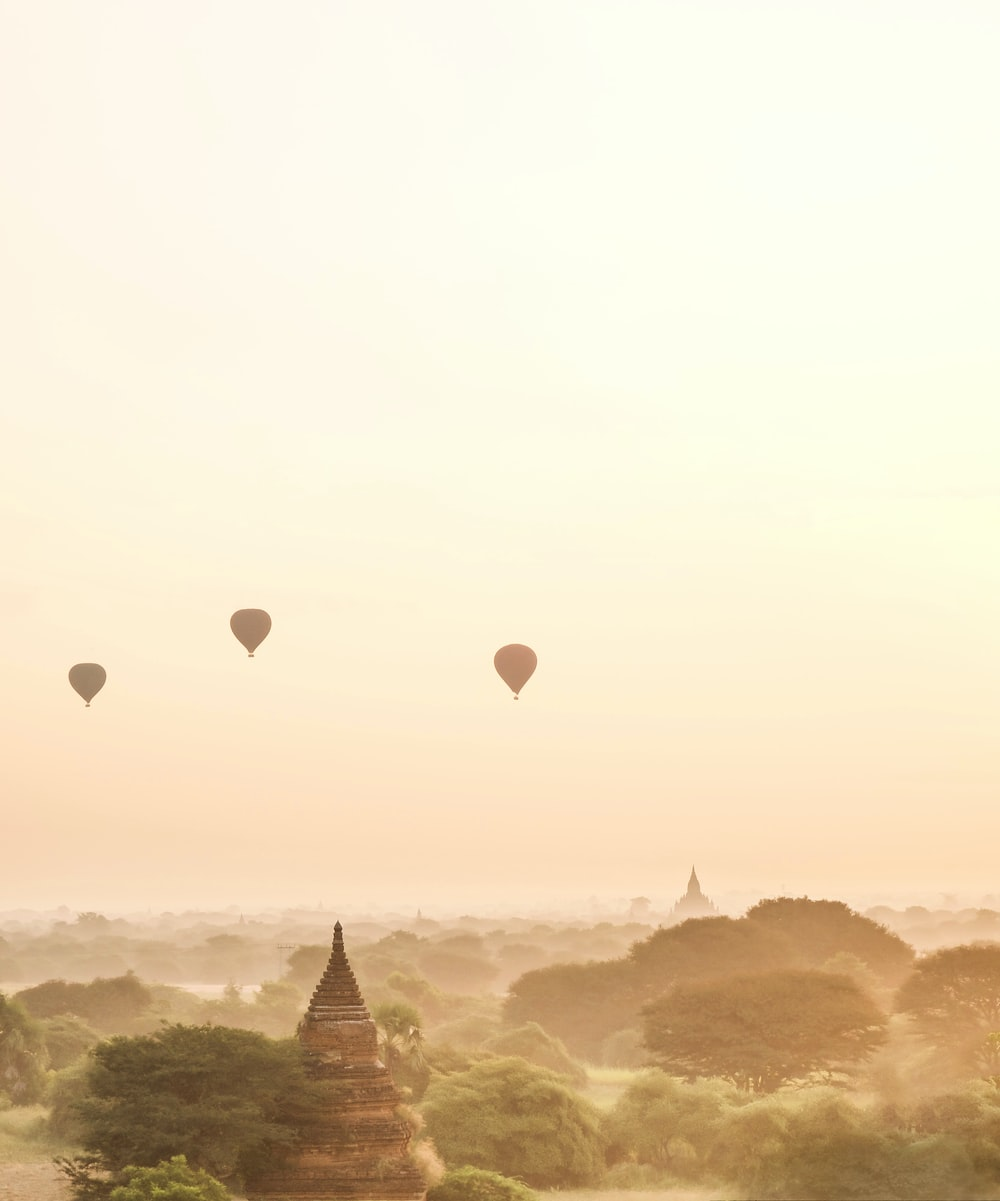 three silhouette of air balloons