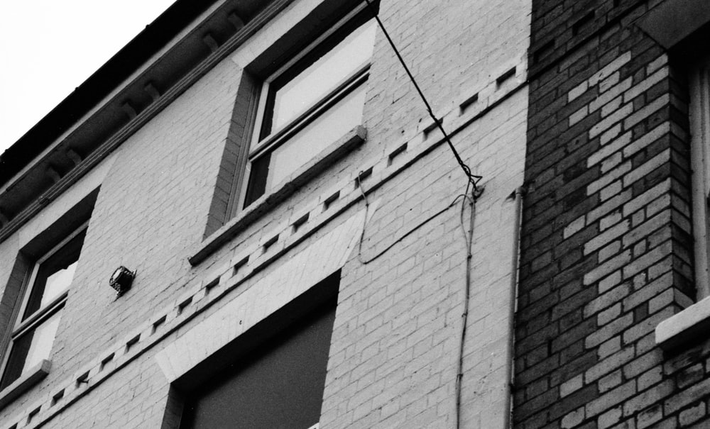 grayscale photo of building closed window