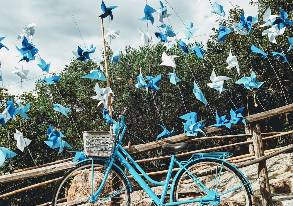 blue bicycle beside brown wooden fence during daytime
