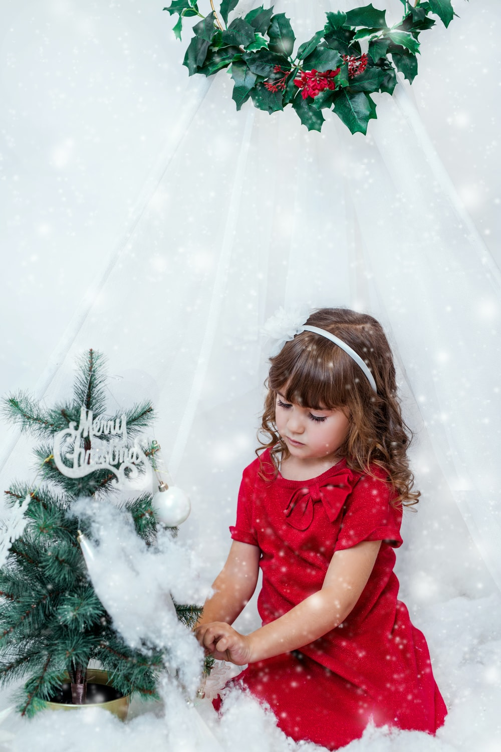 girl wearing red shirt decorating Christmas tree