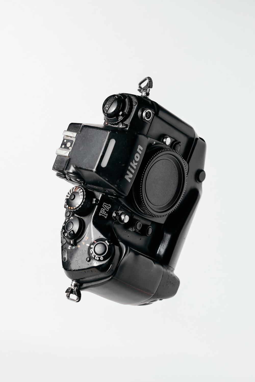 black Nikon DSLR camera on whit surface