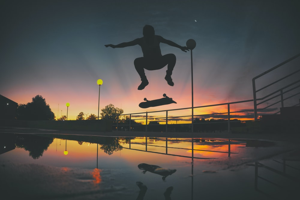 silhouette of skateboard player doing exhibition on park