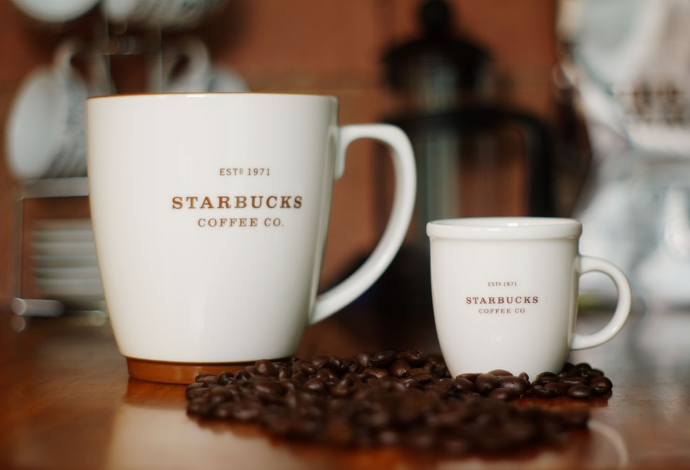 selective focus photography of two white Starbucks ceramic mugs