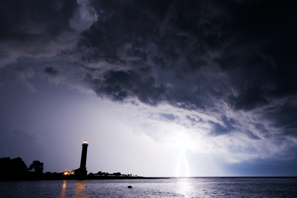 body of water across lighthouse silhouette during nighttime
