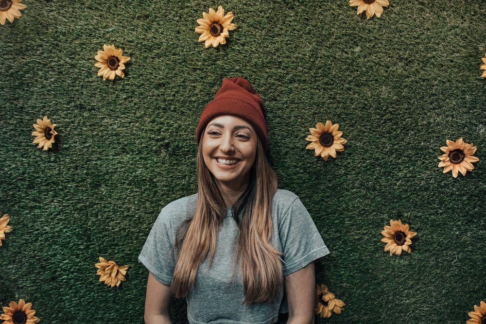 smiling woman leaning on floral wall