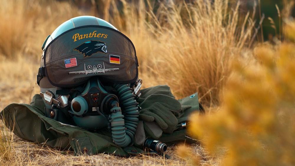grey aviator helmet and gears on grass ground
